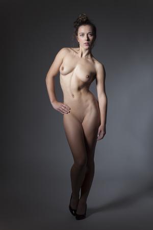 desnudo artistico: Mujer desnuda de pie sobre fondo gris Foto de archivo