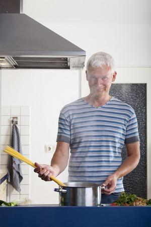 houseman: man cooking pasta in a kitchen
