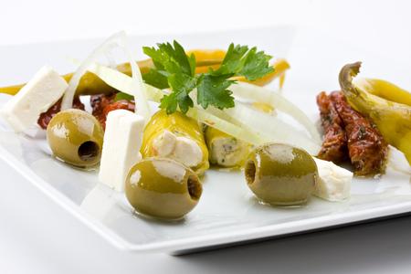peperoni: white plate with antipasti - olives, tomatos and peperoni