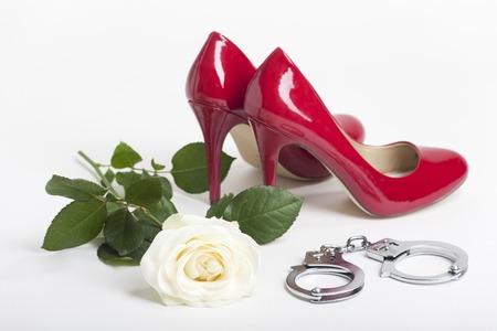 bdsm handcuff: red high heels on white background