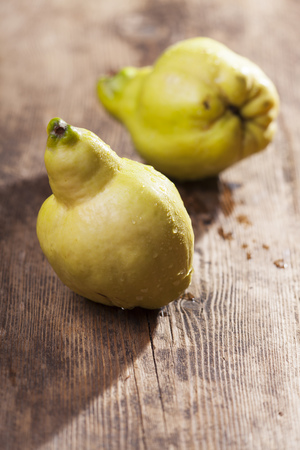 quinces: two fresh quinces on wood