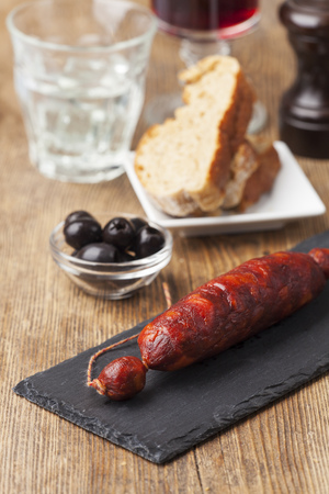 dry sausage: spanish chorizo sausage on black slate Stock Photo