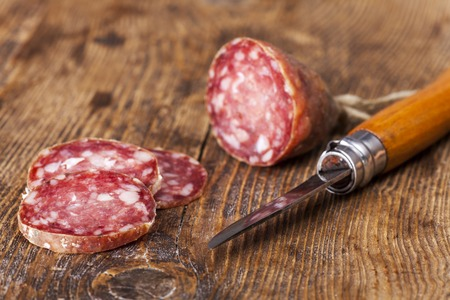 salami sausage with a knife on wood