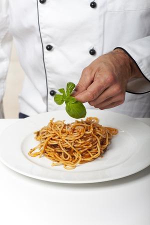 chef decorating a pasta dish