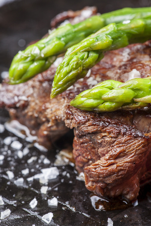 beef steak and green asparagus in a pan  Stock Photo