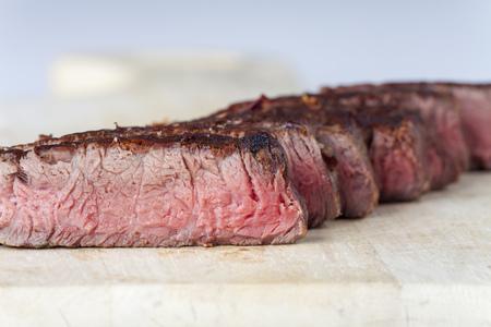 row of medium steak slices on wood