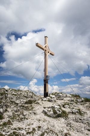 cross on a mountain top with clouds