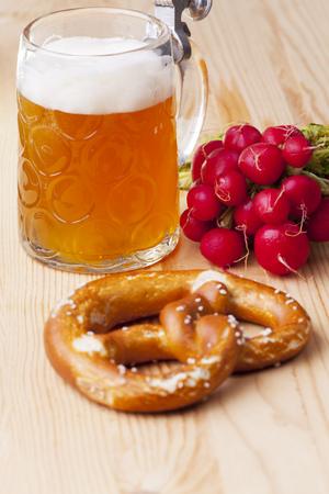 beer, pretzel and radish on rustic wood