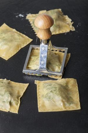 making spinach ravioli on black slate