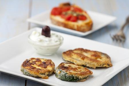 baked zucchini with tsaziki on plates  Stock Photo