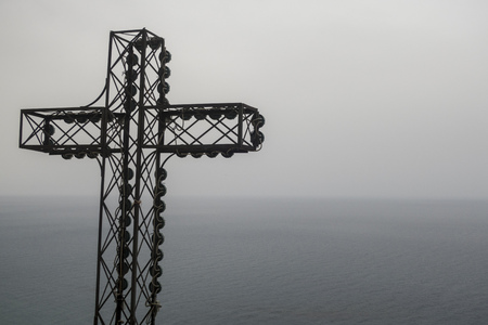 metal cross overlooking the sea in the dusk