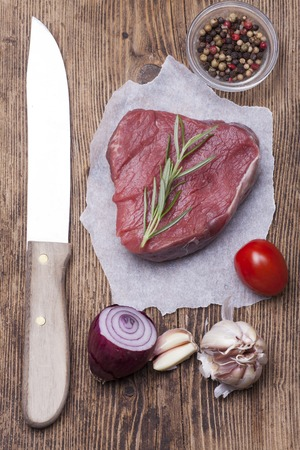 overview of a raw steak on wood