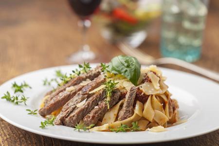 Tagliatelle with steak stripes on a plate