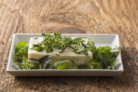 marinating a block of feta cheese with herbs Stock Photo