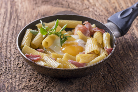 rigatoni with ham and egg in a pan