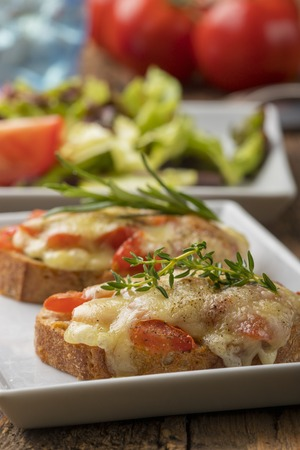 baguette with melted cheese and salad