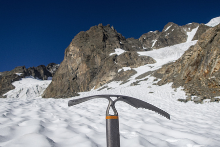 ice axe on a glacier in the alps Stock Photo