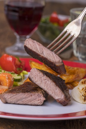 steak on a fork with vegetables Stock Photo