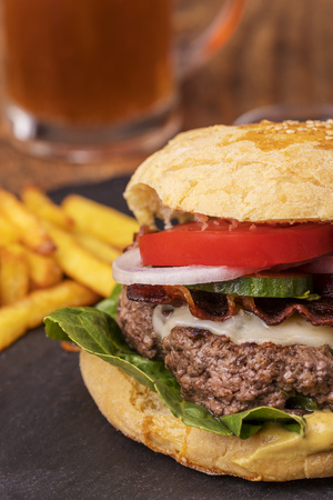hamburger with french fries on slate