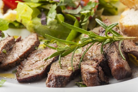 slices of a steak on fresh salad