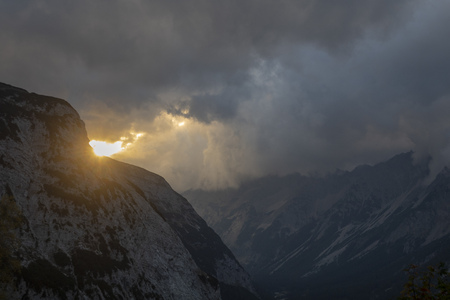 sunlight rays in the alps with clouds