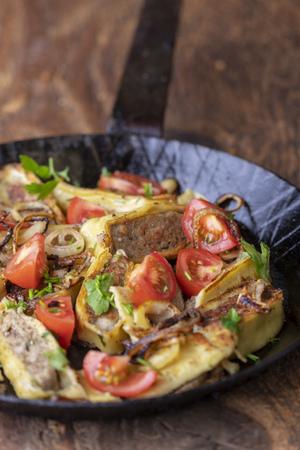 swabian maultasche with onions in an iron pan Standard-Bild - 114427931