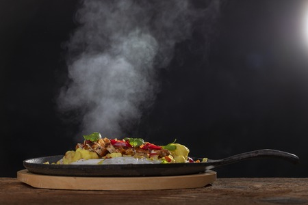steaming hot sizzler on wood Stock Photo