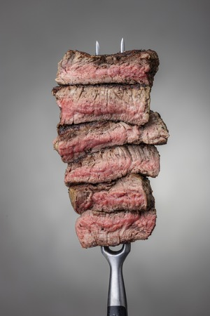 slices of a steak on a fork