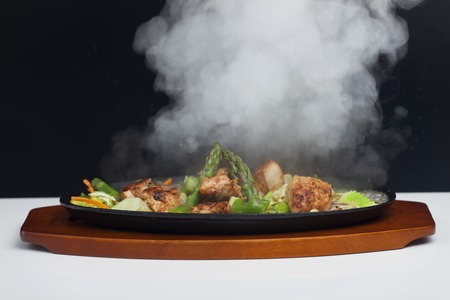 chicken meat with asparagus in a sizzler Stock Photo