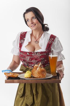 bayerische Frau im Dirndl beim Essen servieren