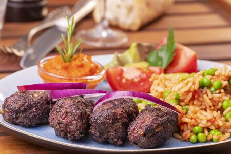 closeup of cevapcici with djuvec rice