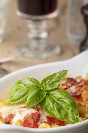 pasta gratin on wood with basil