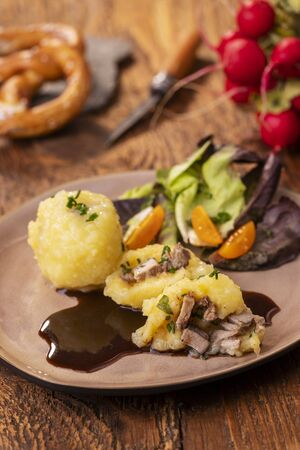 stuffed potato dumplings with salad on wood