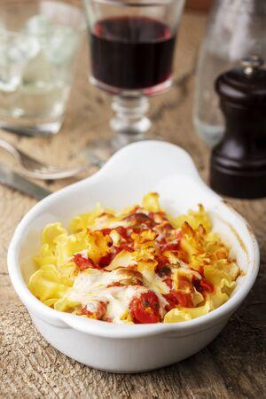 pasta gratin on wood with wine Фото со стока