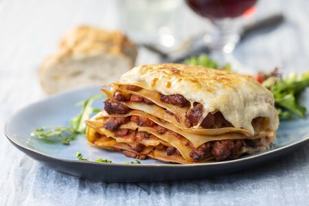 portion of lasagna with wine Stock Photo