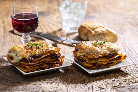 two portions of lasagna on wood