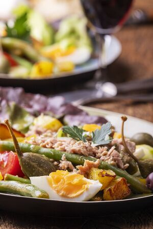 closeup of salade nicoise on dark wood Stok Fotoğraf - 130131161