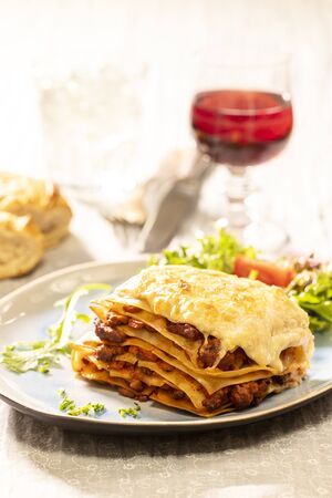 portion of lasagna with wine