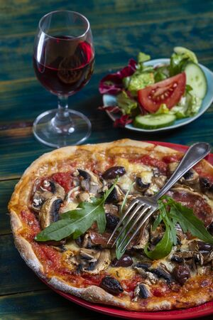overview of a pizza with salad