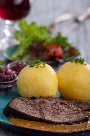 german sauerbraten on a plate with dumplings