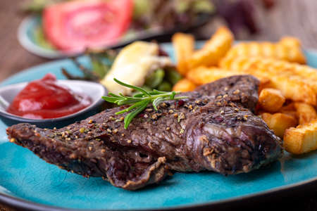 rosemary on a steak with fries