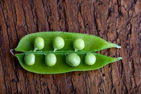 open raw pea pod on wood 免版税图像