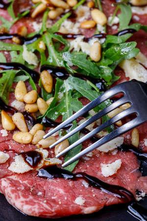fresh carpaccio with arugula on slate 免版税图像