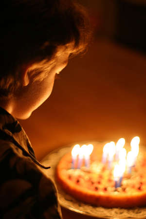誕生日の男の子 - 部屋の唯一の光が来るフロンともしたろうそく。