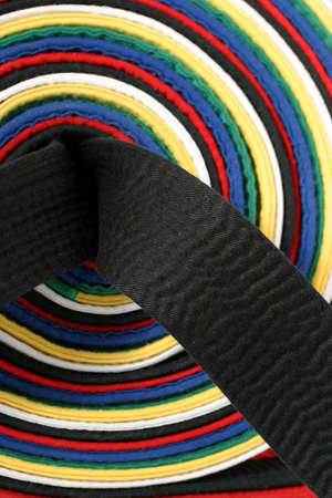 Martial Arts - Close-up on the black belt with the other belt colors used as a background Stock Photo - 587801