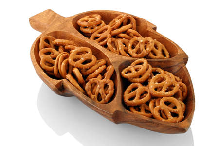 Pretzels - Cocktail snack presentation in a wooden dish carved in the shape of a leaf. Stock Photo