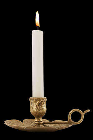 Brass Candleholder - Decorative antique brass candelabra with brightly lit white pillar candle.  Isolated over black. photo