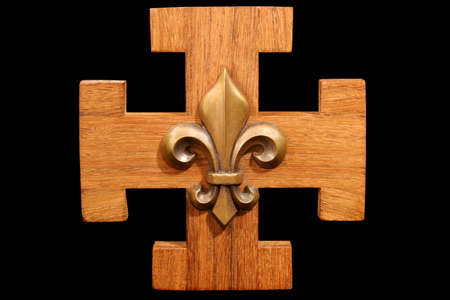 French Scout Emblem - Antique scouting fleur-de-lis on solid oak wood. Isolated on black.