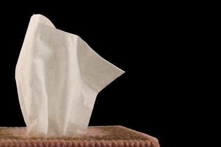 Tissue Box - black background - close-up of paper handkerchief in a decorative plastic canvas box. Stock Photo