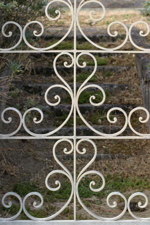 wrought: Wrought Iron Gate - Decorative gate opens on stone stairs leading to an abandoned French seaside villa.